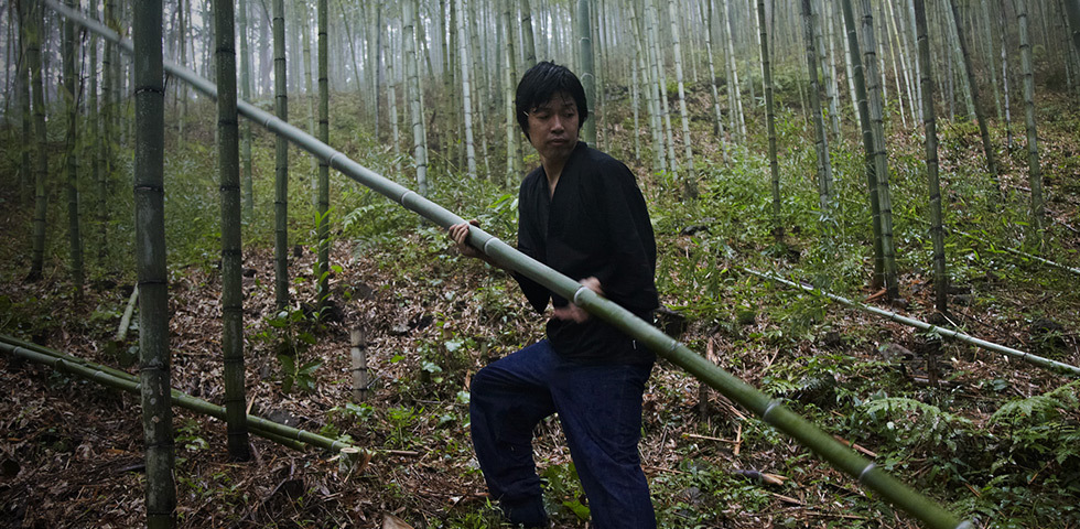 Tanabe Chikuunsai IV carrying bamboo log in a bamboo grove.